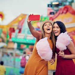 Girlfriends taking selfie at a summer carnival