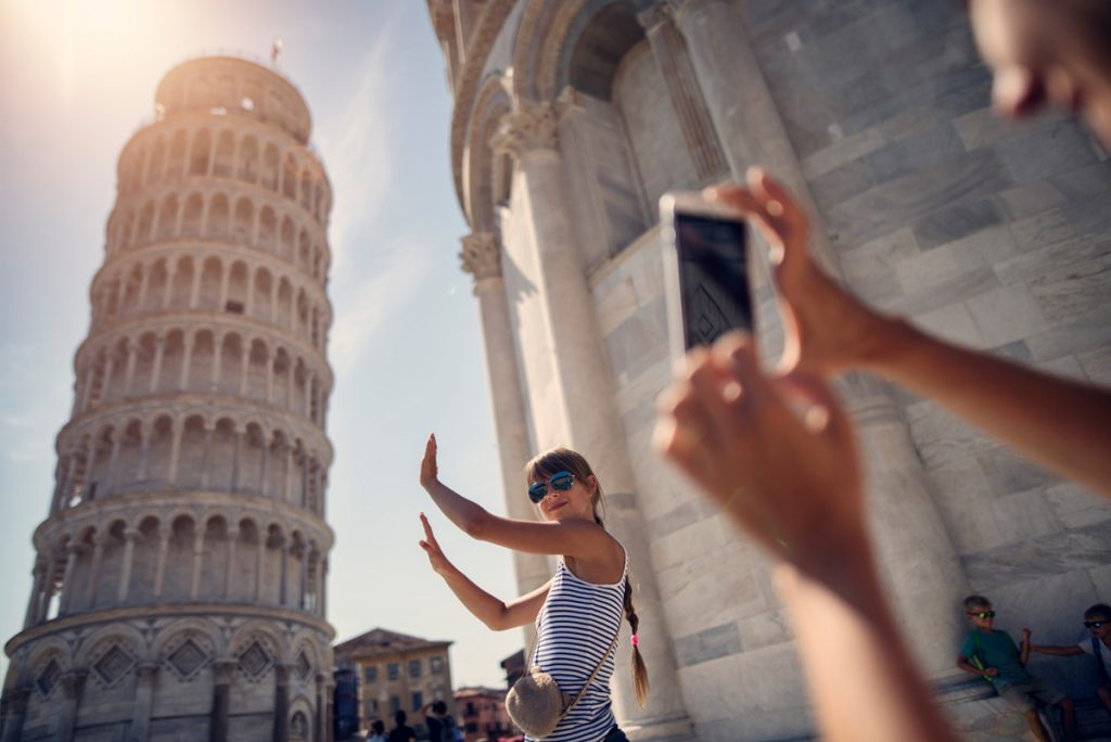 Girl pretending to hold up the leaning tower of Pisa