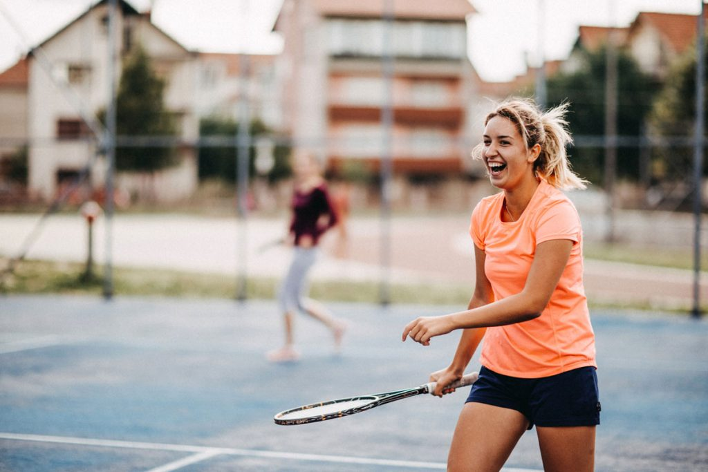 A portrait mode photo of two girls playing tennis | Motif