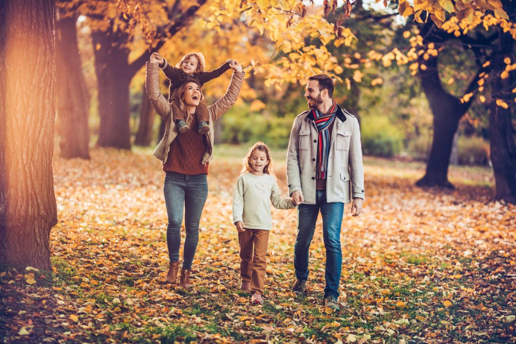 Family walking through fall trees during golden hour