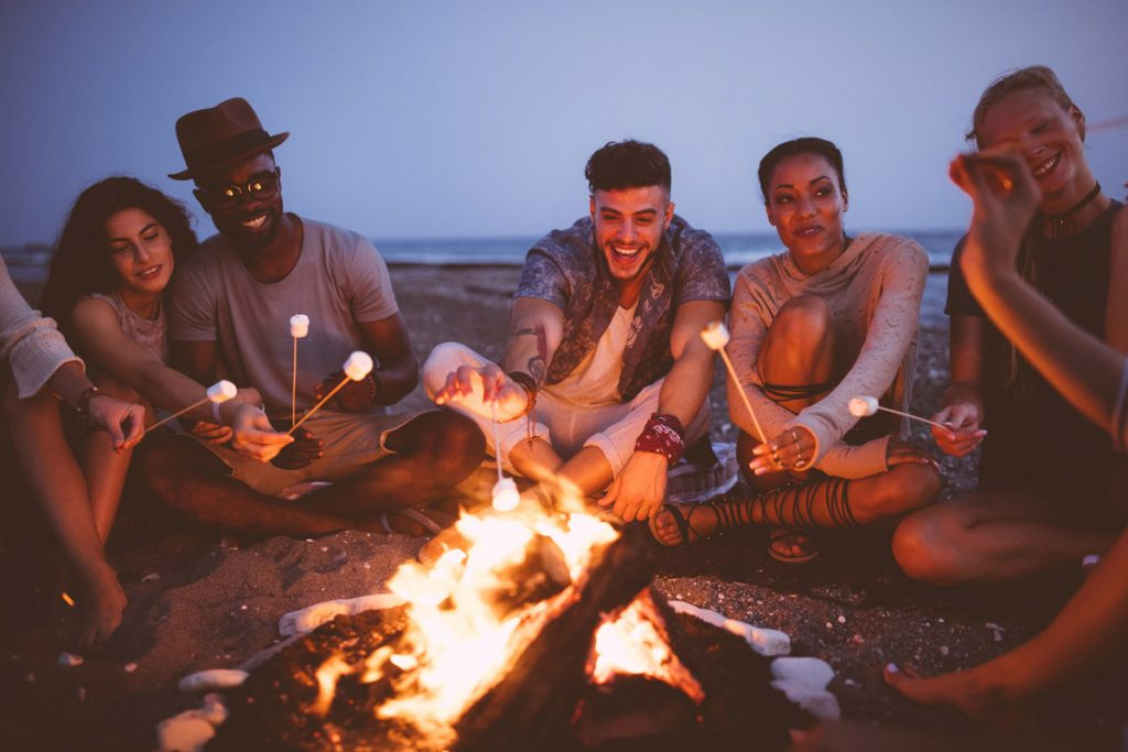 Friends enjoying a bonfire on the beach