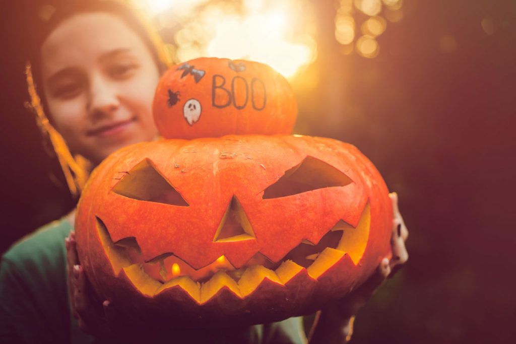Girl holding up Jack-O-Lantern for the camera