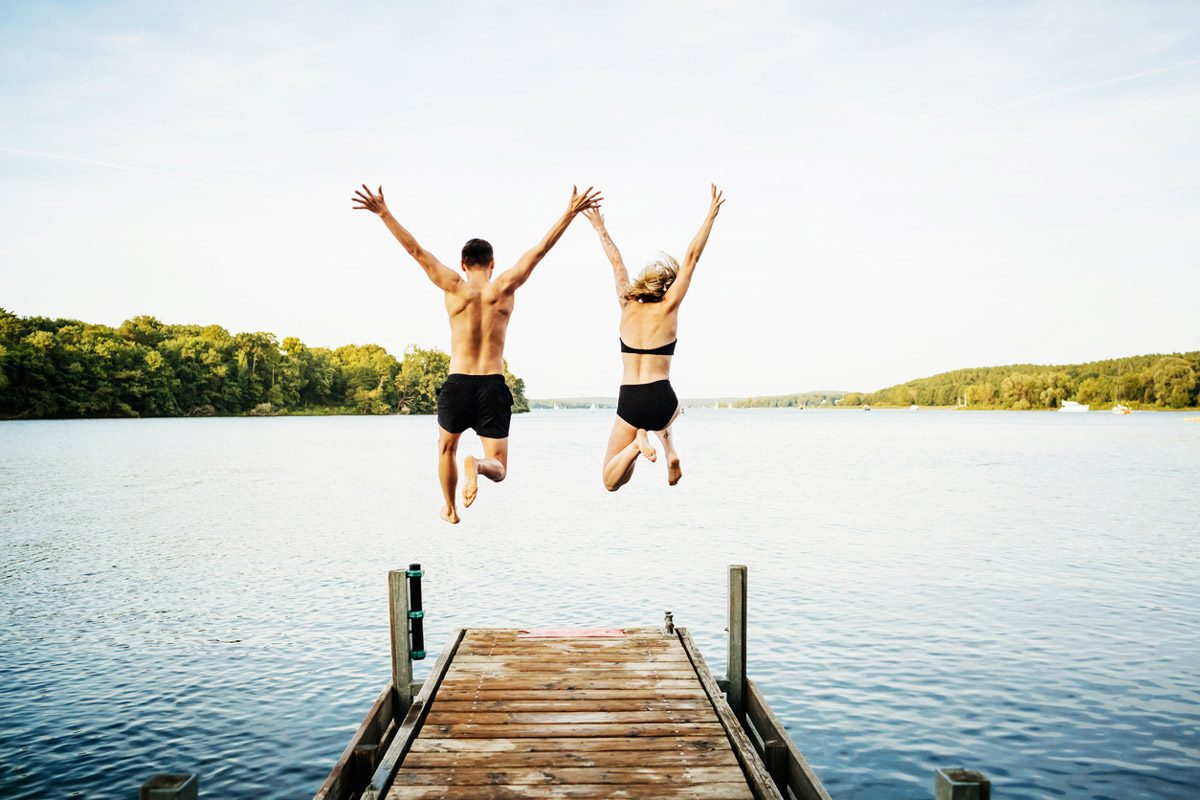Two friends jump off a pier into the lake