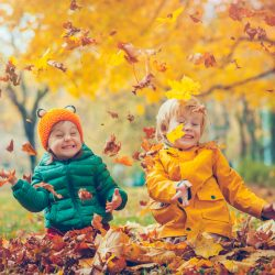Kids playing in leaves in autumn.