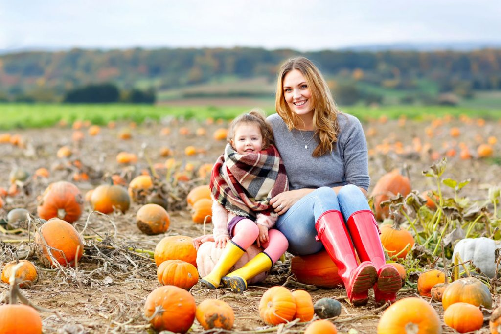 Mother and daughter sitting in a pumpkin patch