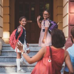 Sisters waving goodbye to Mom and Dad on their first day of school