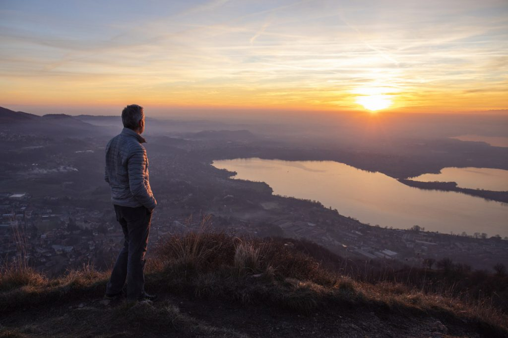 Hiker watches a sunrise at the top of a large hill.