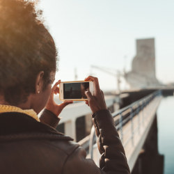 Tourist taking photograph of a bridge with her iPhone
