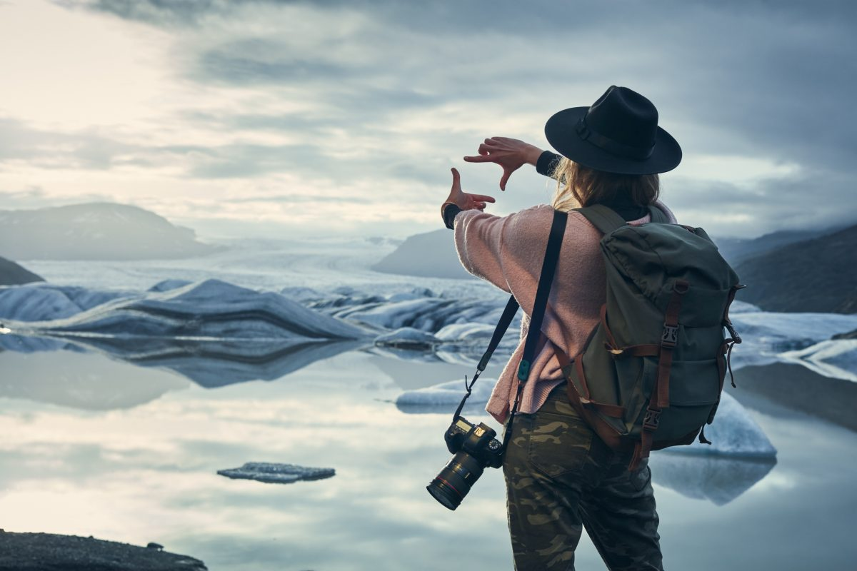 Female photographer at glacier lagoon. Sunset