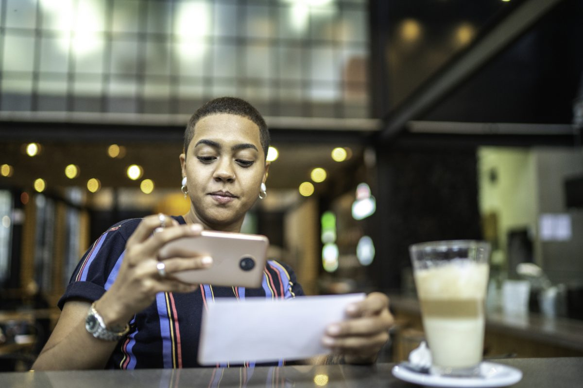 Young woman depositing check by phone in the cafe