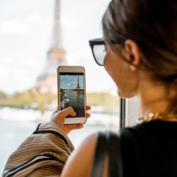 Woman photographing eiffel tower in Paris
