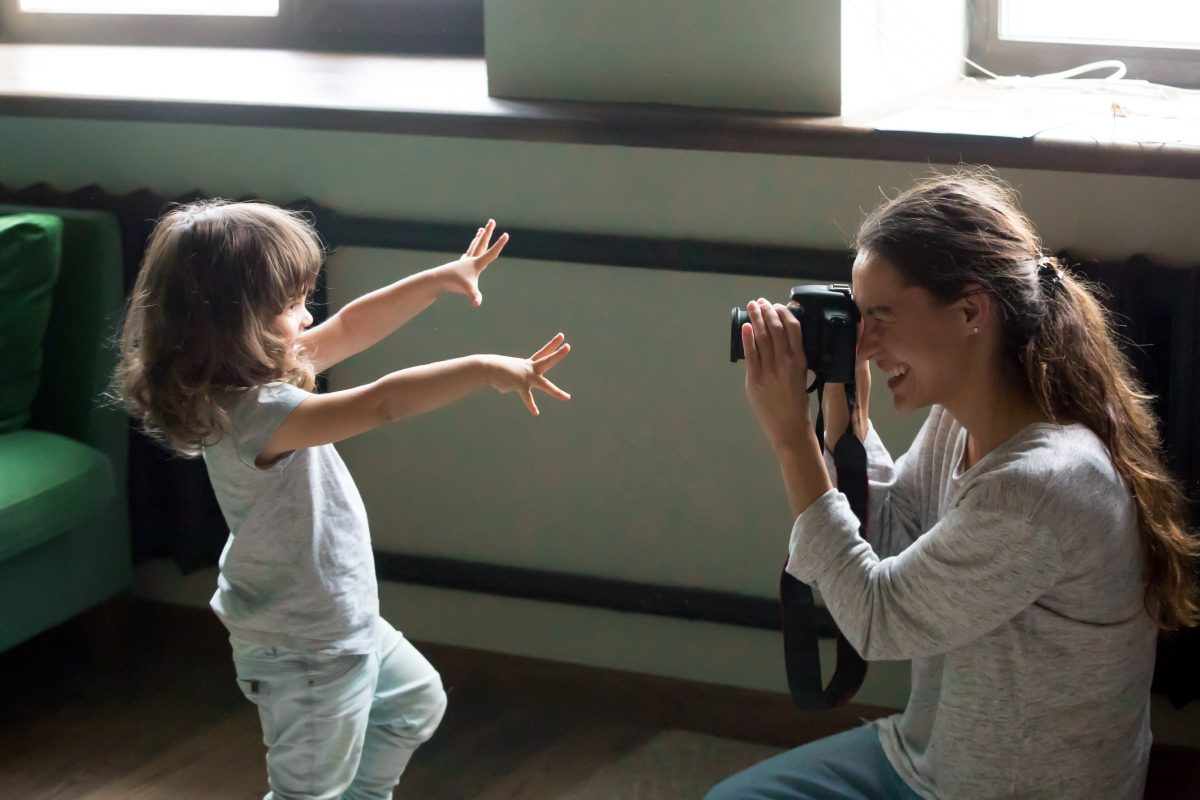 Mom photographer making photo of kid daughter on digital camera