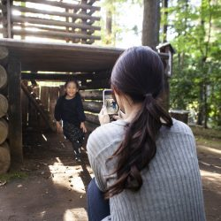 A girl playing at a campsite. Mother shooting pictures with smartphone.