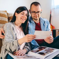 Newlyweds are looking at wedding photo album together | Motif