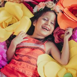 A little girl with oversized craft flowers.