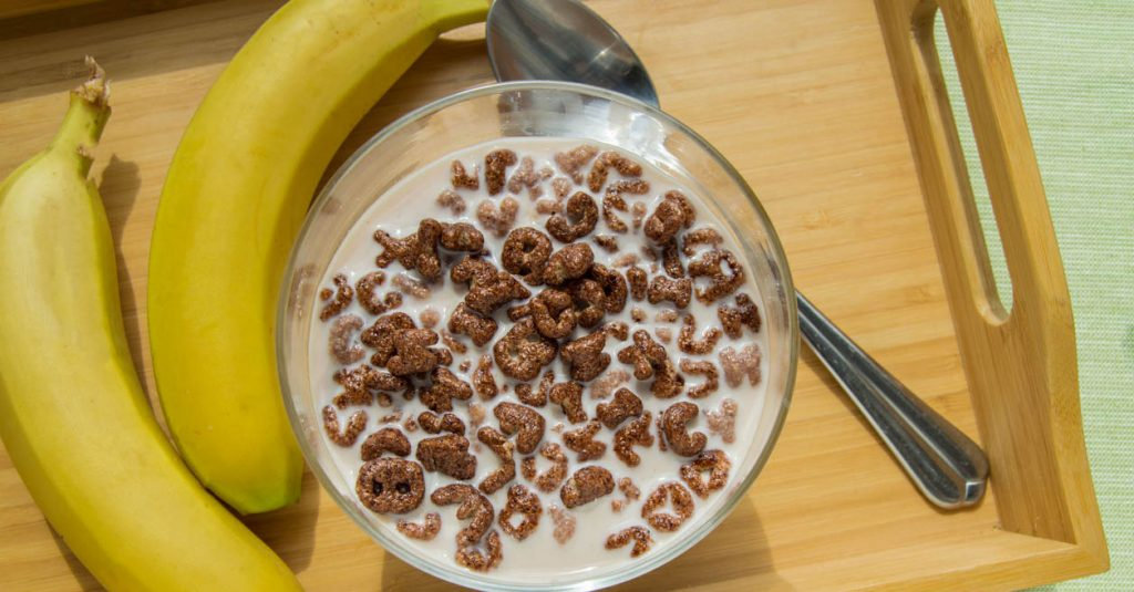 Bowl of oatmeal chocolate flakes in the shape of letters of the alphabet with milk on a wooden tray with bananas, healthy Breakfast concept