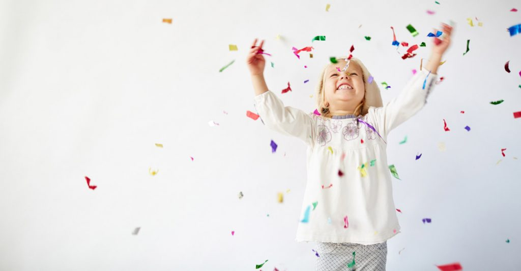 Ecstatic little girl catching falling confetti
