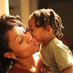 A young daughter giving her mother a kiss.