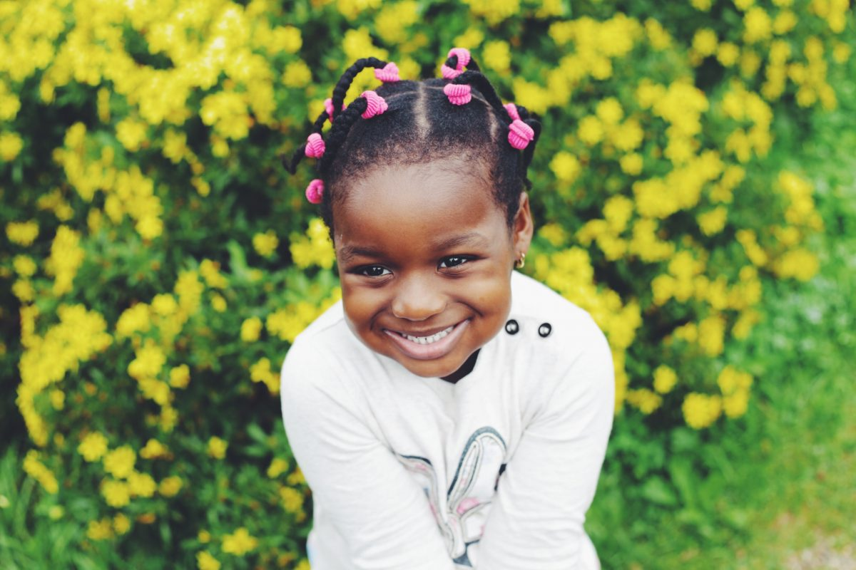 A little girl smiling in front of a wall of flowers.