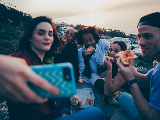 A group of friends taking a selfie while having a picnic.