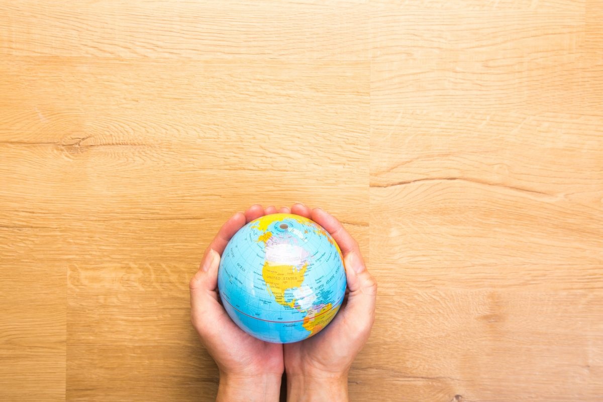 Holding a small globe in your hands.