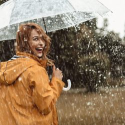 Cheerful pretty girl holding umbrella while strolling outside.