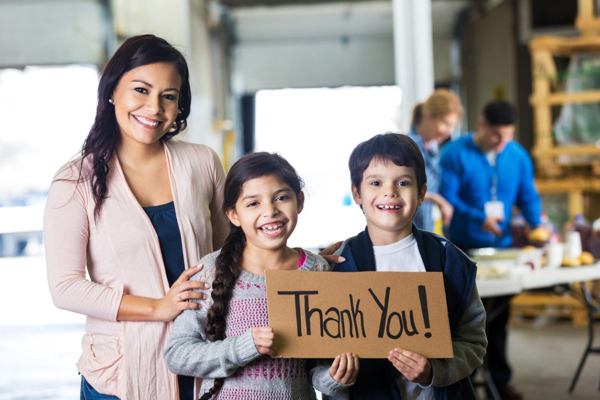 Mother and elementary age children holding THANK YOU sign