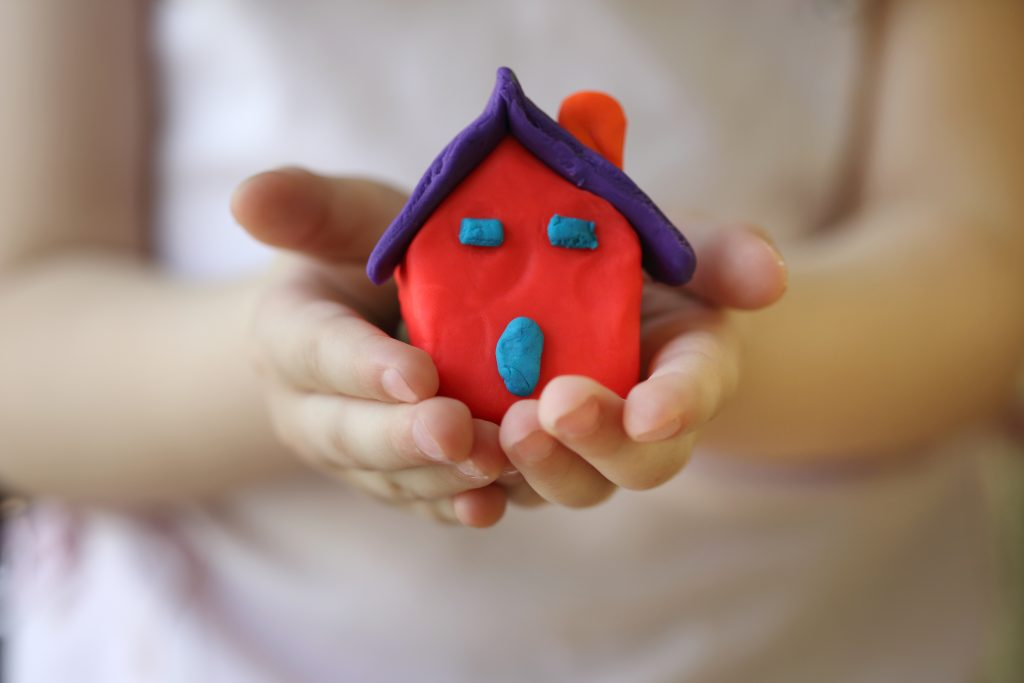 Take a closeup of your child holding house-shaped clay art for their art photo book.