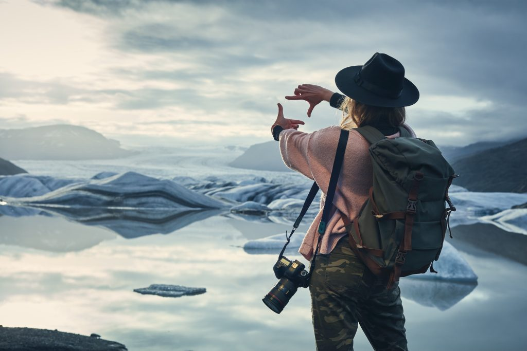 A photographer finds the focus of their glacier image using their two forefingers.