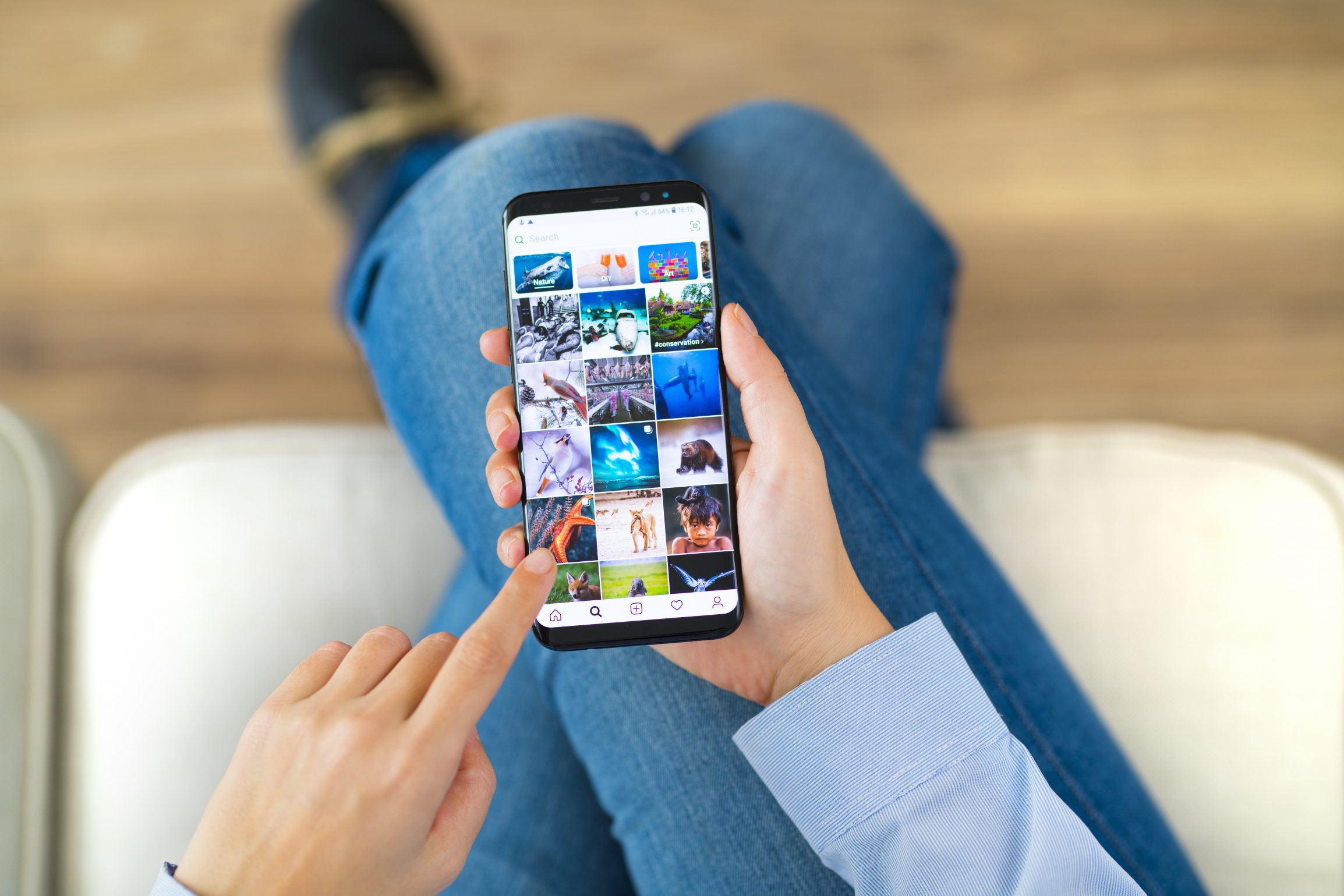 Woman scrolling Instagram feed, deciding which pictures to use in square photo book.
