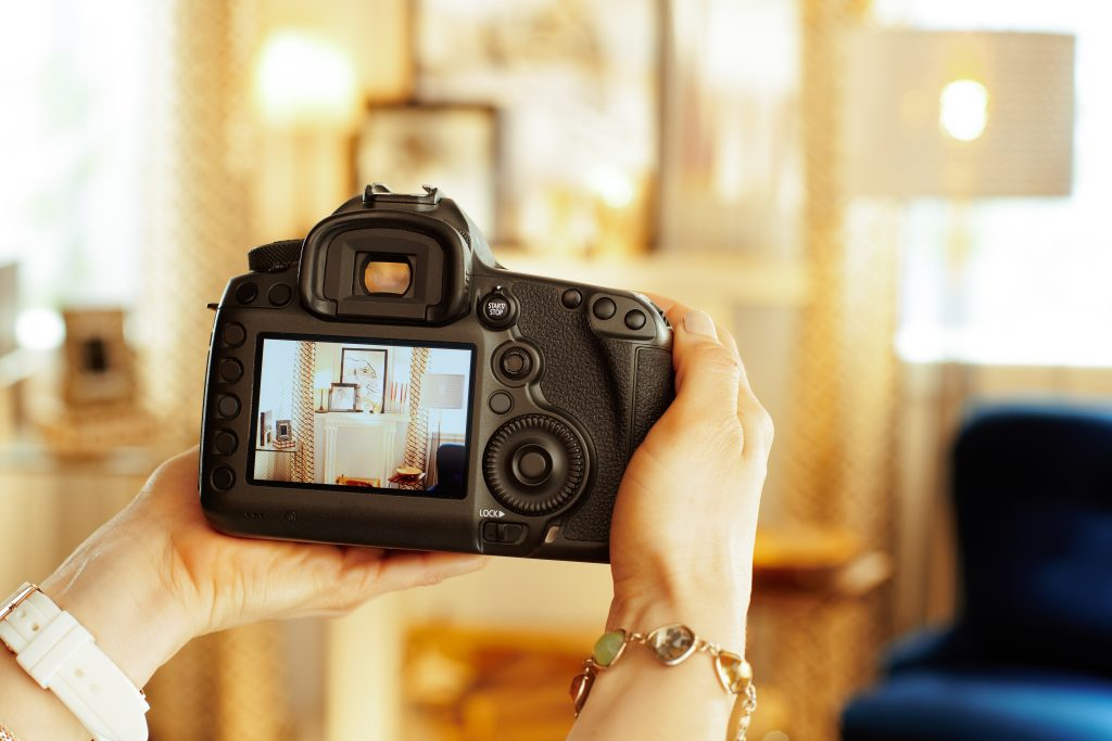 A woman holding a DSLR shows off the camera's viewfinder.