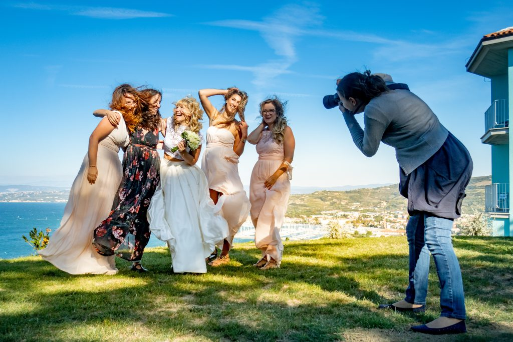 A wedding photographer captures a candid photo of the bride and bridesmaids laughing.