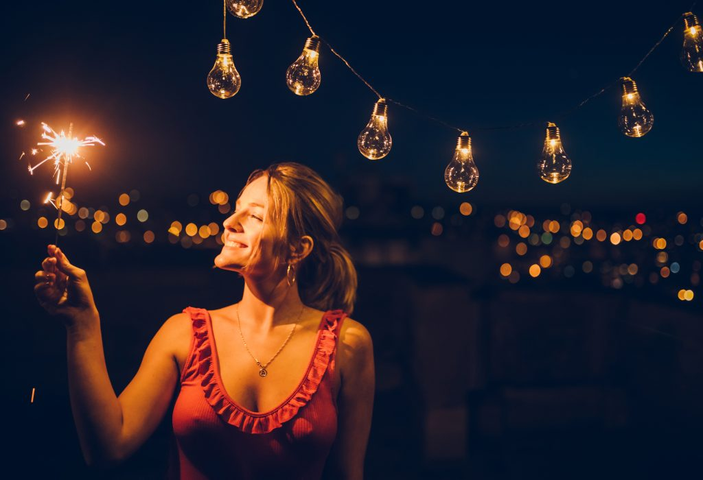 A sparkly summer photoshoot idea: woman with a sparkler standing under string lights.