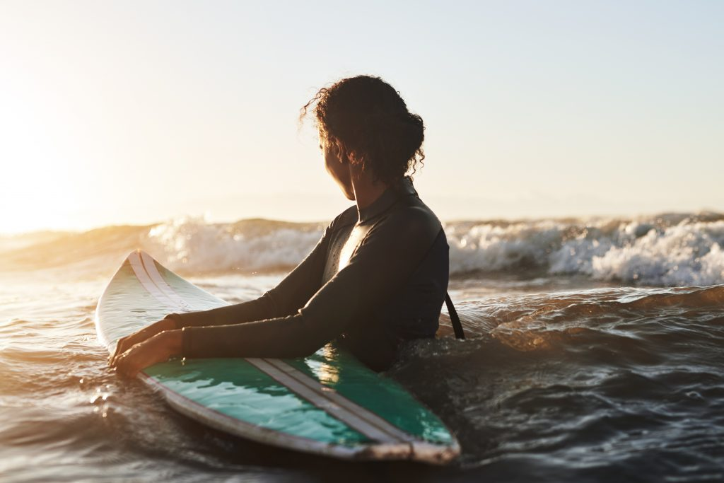 Get in the water with a surfer catching waves to stay cool while taking summer photos.