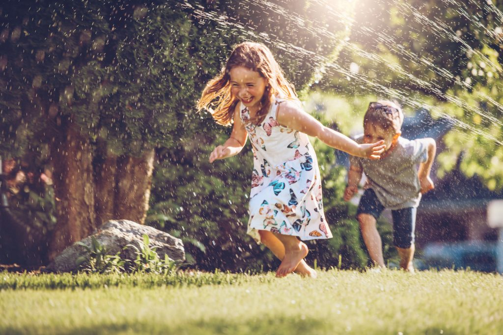 Include two kids running through a sprinkler in your summer photoshoot ideas.