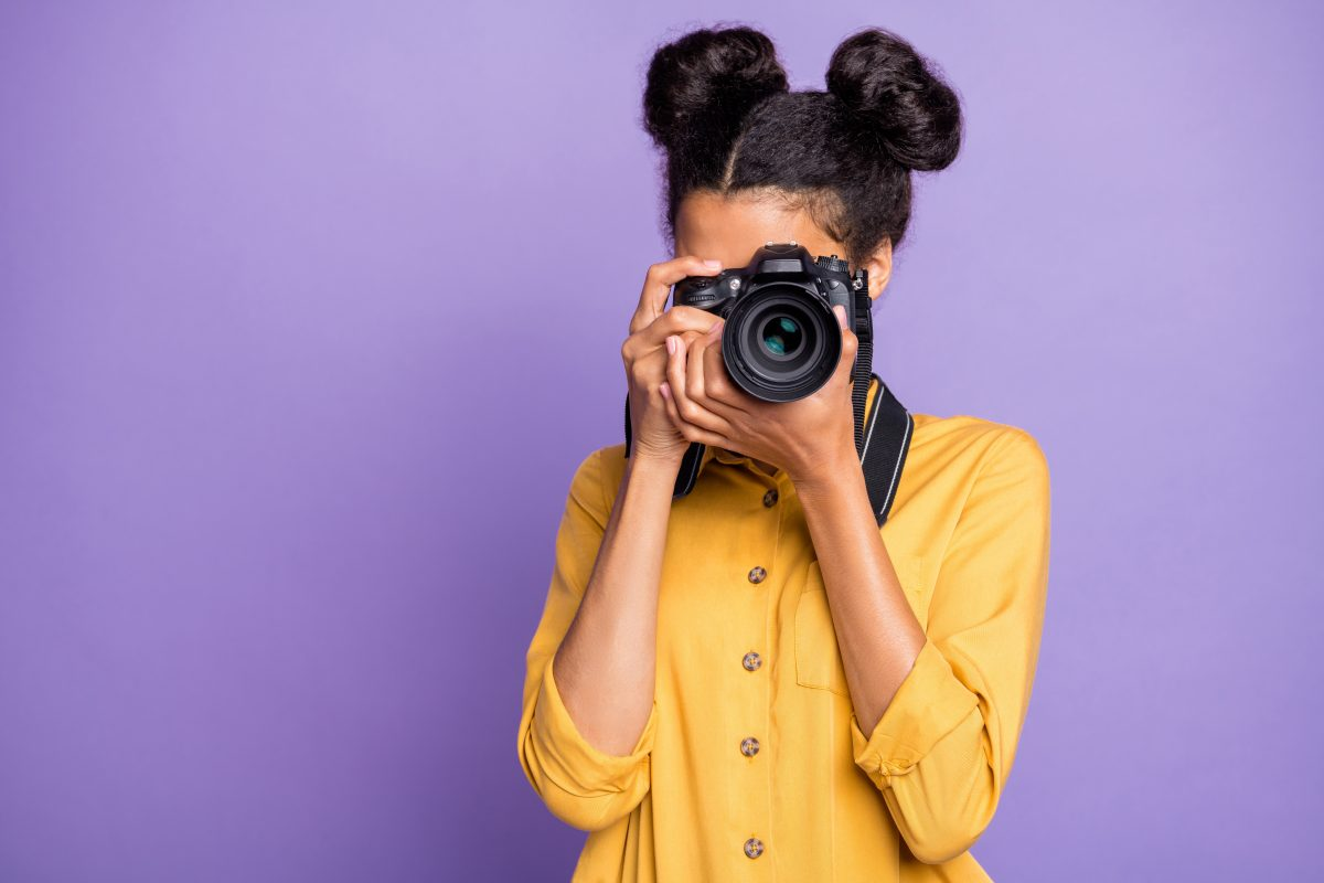 A female photographer has read her photography dictionary and is pointing, ready to shoot.