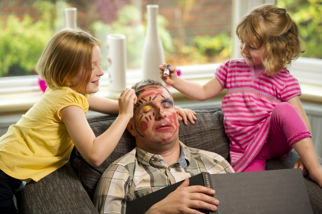 Combine a funny photo book caption with a pic of kids doodling on Dad while he sleeps.