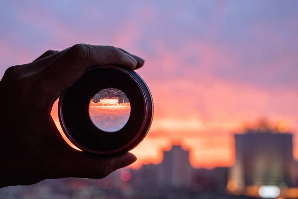 Use the right camera lens to capture nature photography, like this sunset over a city skyline.