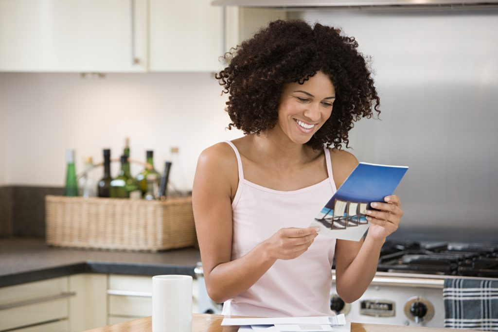 Reading a thinking of you photo card in her kitchen put a smile on this woman's face.