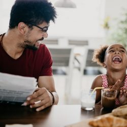 Man makes his little girl laugh with dad jokes that also make great photo book captions.