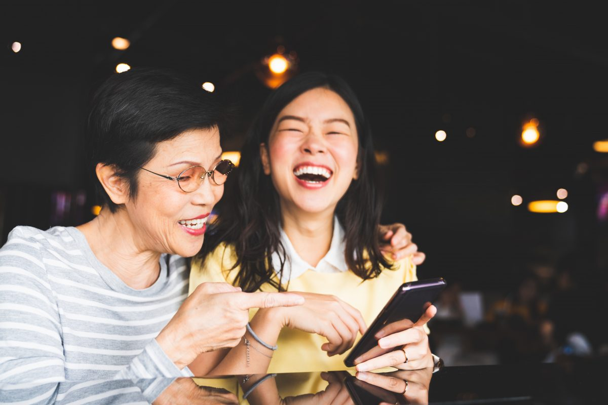 Asian mother and daughter laugh at memories in their Apple Photos organization.