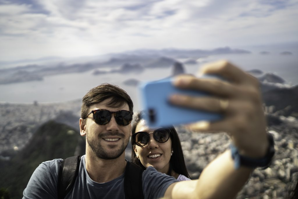 Young couple takes a selfie with iPhone, which automatically saves to digital photo storage.