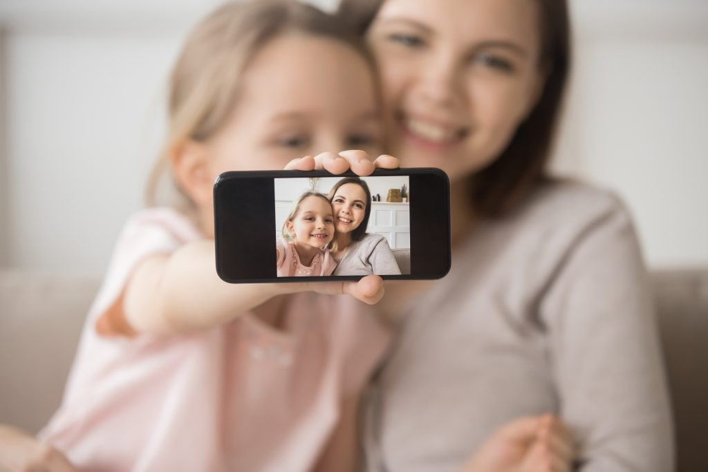 Happy mother and daughter follow key selfie tips by using rear-facing camera to take a quality photo
