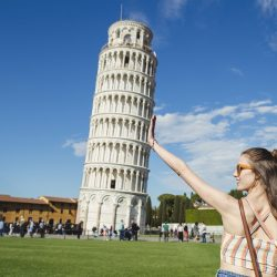 Young woman holding up Leaning Tower of Pisa is classic forced perspective photography.