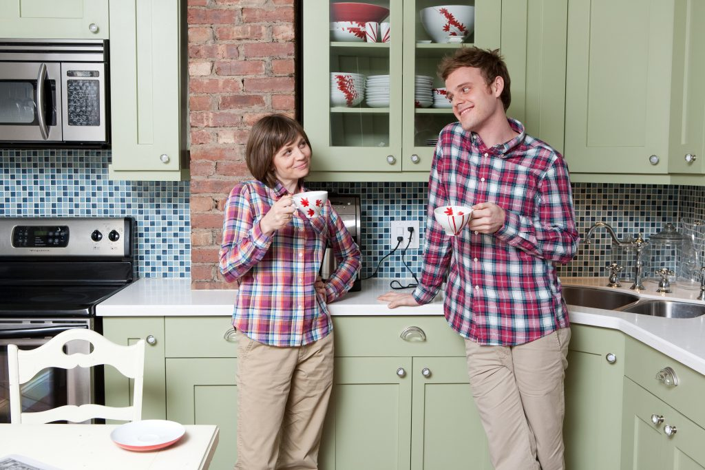A young couple dressed in matching plaid shirts and khakis take funny selfie pose in the kitchen.