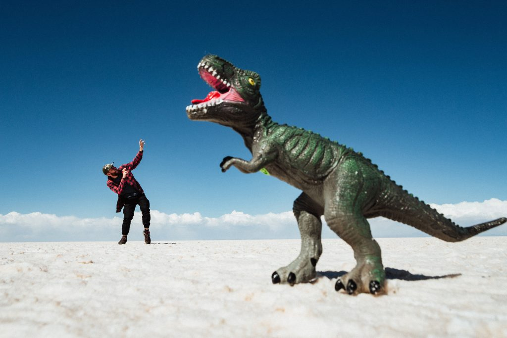Man creates funny selfie idea, where it looks like toy dinosaur is attacking him outside.