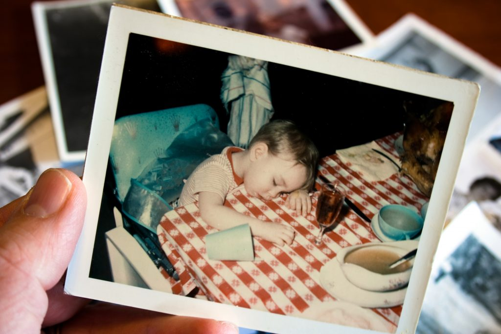 Recreating a childhood photo, where you fell asleep at the dinner table, is a funny selfie idea.