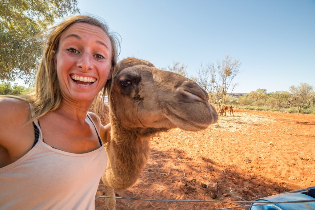 Fun photo ideas include animals, like this woman taking a selfie with a camel in the desert.