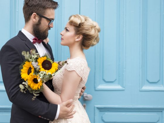 Newlyweds embrace in contrasting color photography, where sunflower bouquet contrasts blue doors.