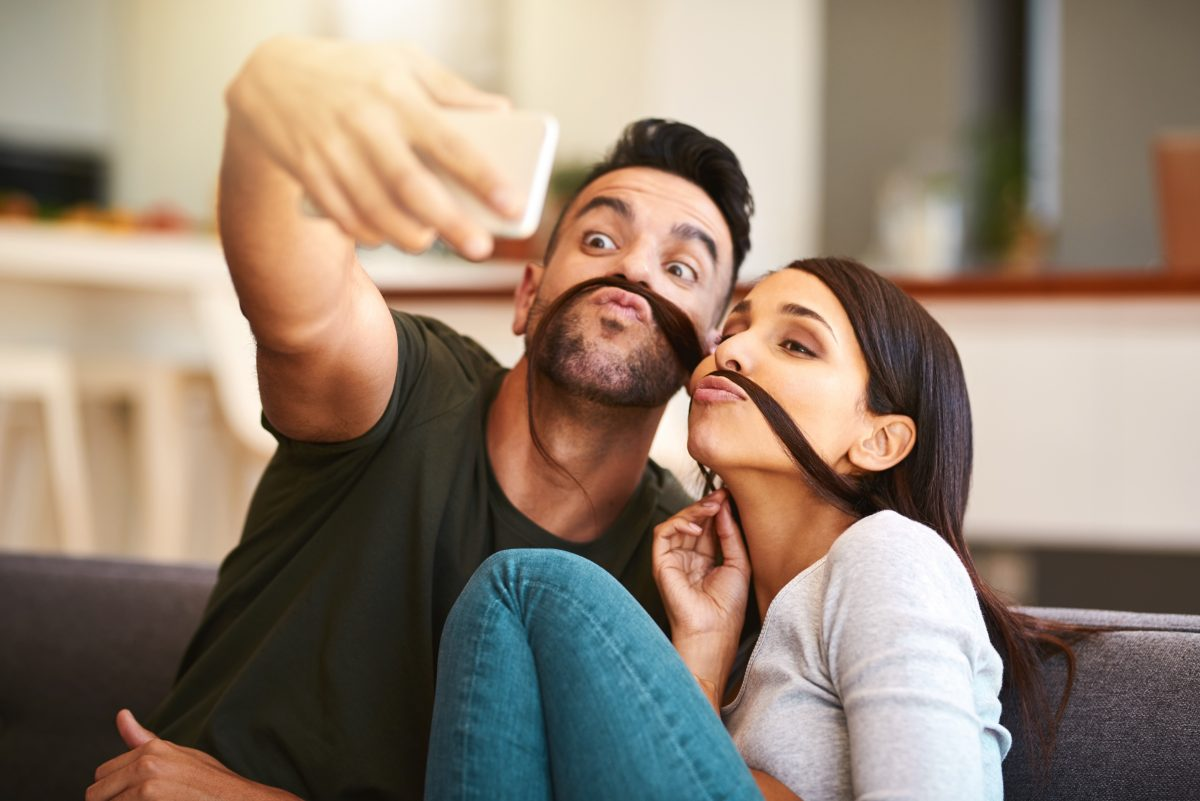 Young couple creates funny selfie ideas by wrapping woman's hair around upper lip like a mustache.